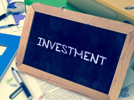 Investment Concept Hand Drawn on Chalkboard on Working Table Background. Blurred Background. Toned Image. 3D Render.