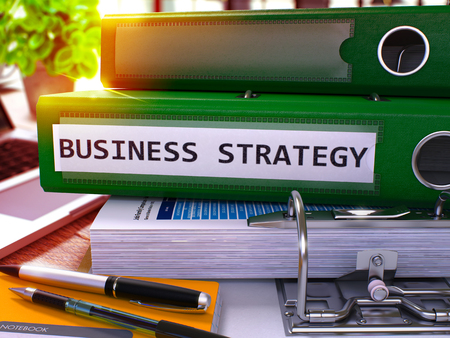 Business Strategy - Green Office Folder on Background of Working Table with Stationery and Laptop. Business Strategy Business Concept on Blurred Background. Business Strategy Toned Image. 3D.