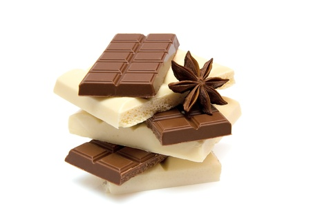 slices of black and white chocolate with anise on white background