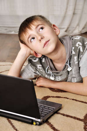 Photo pour Happy little boy with laptop lying on the floor at home - indoors - image libre de droit