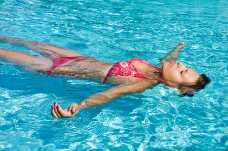 Photo pour Young girl is swimming in a pool in sunny day - image libre de droit