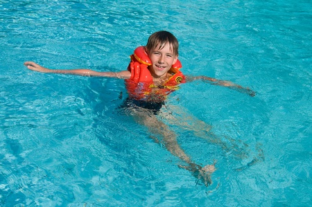 Boy in life jacket is learning to swim in the swimming pool