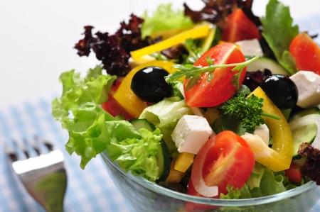 Foto de Greek salad in glass bowl on wooden background closeup - Imagen libre de derechos