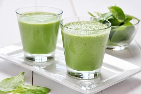 Spinach smoothies in glass on a wooden backgroundの写真素材