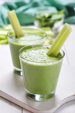 Green vegetable smoothie with celery and spinach on wooden background