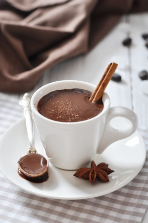 Hot Chocolate in cup with cocoa powder and cinnamon stick on wooden background