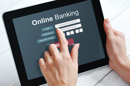 Female hands using online banking on touch screen device