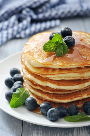 Foto per Pancakes with fresh berries, mint and maple syrup on white plate closeup - Immagine Royalty Free