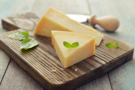 Parmesan cheese on cutting board with basil and knife on wooden background