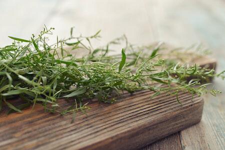 Fresh tarragon on wooden cutting board closeup