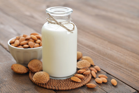 Photo pour Almond milk in bottle with nuts on wooden background - image libre de droit