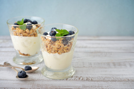 Granola with yogurt and blueberry in glass on wooden background
