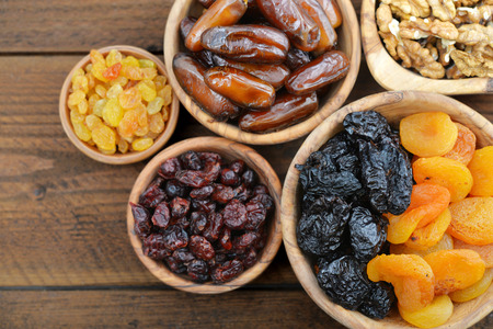Mix of dried fruits and nuts in wooden bowls closeup