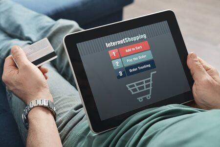 Photo pour Male hands using touch screen device for online shopping - image libre de droit