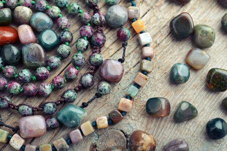 Beautiful semiprecious stone beads on wooden background closeup