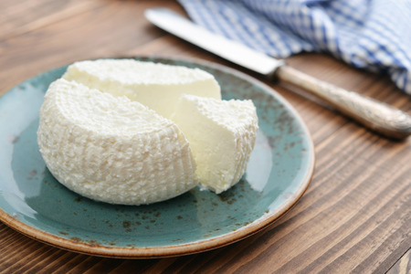 Fresh ricotta on plate on wooden background