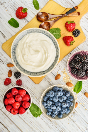 Greek yogurt in bowl with fresh berries and almond on white wooden background, top view