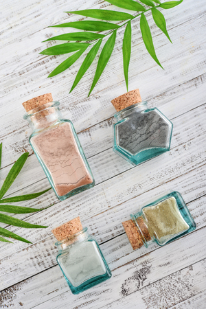 Photo pour Different cosmetic clay in vintage jars on wooden background, top view - image libre de droit