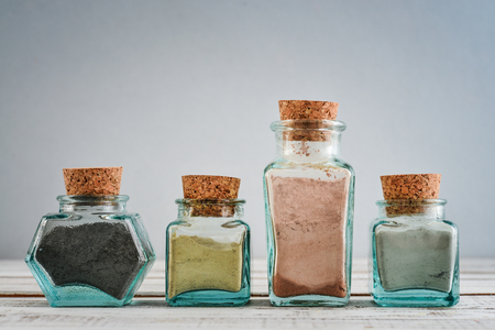 Photo pour Different cosmetic clay in vintage jars on wooden background - image libre de droit