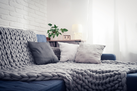 Photo pour Gray knitted blanket from merino wool on couch with pillows in the interior of the living room - image libre de droit