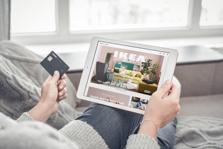Photo pour Kiev, Ukrain - February 10, 2018: Woman using IKEA app on a brand new Apple iPad Pro Silver to order furniture. IKEA was founded in of Sweden in 1943, IKEA to have large chain stores around the world. - image libre de droit