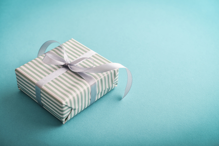 Photo pour One striped  gift box with grey ribbon on blue background  closeup - image libre de droit