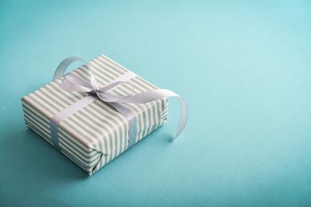 Foto de One striped  gift box with grey ribbon on blue background  closeup - Imagen libre de derechos