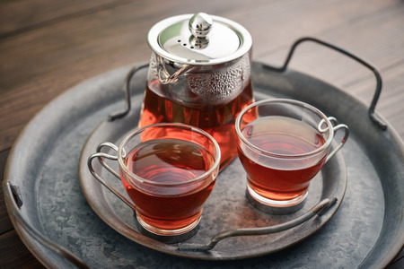 Foto de Two glass cup of tea with teapot on round vintage metal tray on wooden background - Imagen libre de derechos