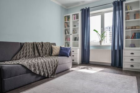 Photo pour Light cozy teen room with white bookcases,  grey sofa and blue walls  - image libre de droit