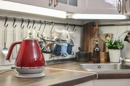 Photo pour Red electric kettle in retro slile  in kitchen interior closeup - image libre de droit
