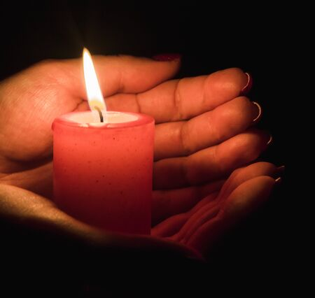 Photo pour Female hands holding a burning candle in the dark - image libre de droit