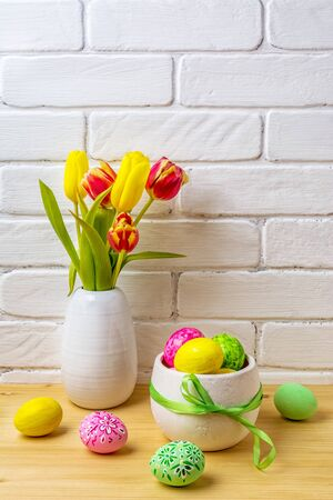 Photo pour Easter arrangement with pink, green, yellow hand decorated eggs, red and yellow tulips in the white vase  - image libre de droit