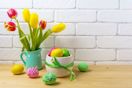 Photo pour Easter rustic centerpiece with decorated eggs, green ribbon, red and yellow tulips in the polka dot mint green jug near painted brick wall - image libre de droit