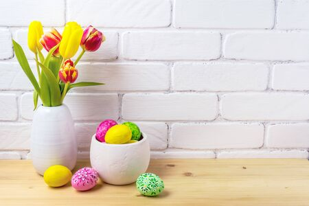 Photo pour Easter rustic arrangement with decorated eggs, red and yellow tulips in the white vase near painted brick wall - image libre de droit