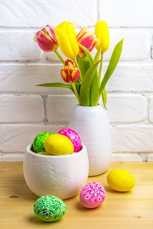 Photo pour Easter table centerpiece with decorated pink, green, yellow eggs and tulips in the white vase near painted brick wall - image libre de droit
