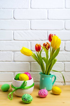 Photo pour Easter arrangement with red, yellow tulips in the mint green pitcher and decorated eggs near painted brick wall - image libre de droit