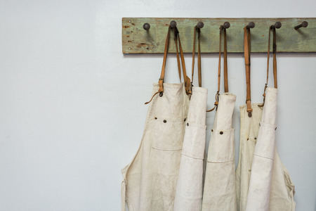 white apron clothes hanging on the wall