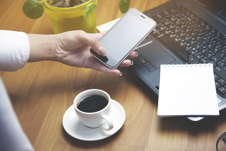 Business woman hand working and smart phone and laptop on wooden desk in office