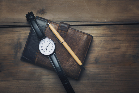 elegant watch and wallet on table