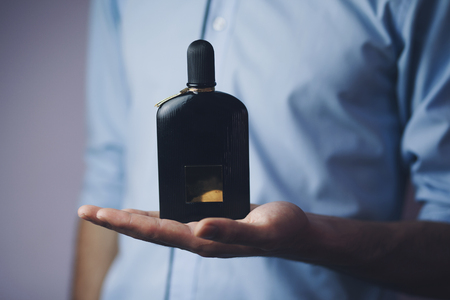 Handsome young businessman using perfume