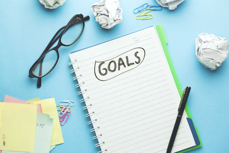 Goals text on notebook with gl on blue background