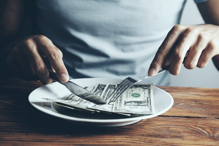 Hands cut money on plate reduce funds concept