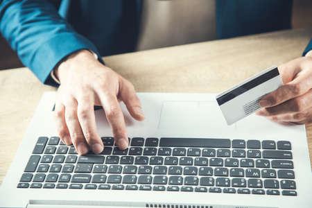 Photo pour man hand credit card and computer on the desk - image libre de droit