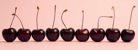 Photo pour a row of cherry berries of 9 pieces, standing in a line on a pale peach background, banner - image libre de droit
