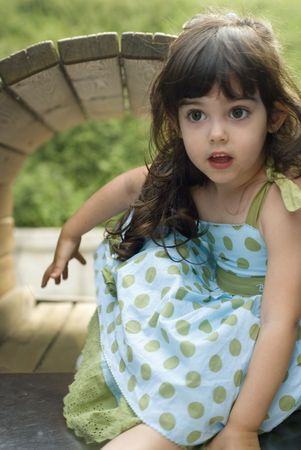 Outdoor portrait of a cute little caucasian girl child discovering nature in the garden