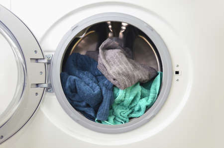 Photo pour Washing machine with open door and loaded with colorful clothes - image libre de droit