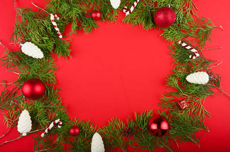 Photo pour Christmas frame made of green branches, festive decorations and pine cones on red table. - image libre de droit
