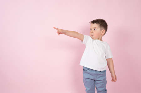 Photo pour Surprised boy pointing up to empty place on pink backgroun, copy space for advertising product. High quality photo - image libre de droit