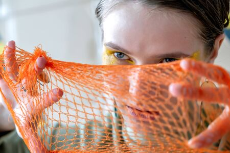 Photo for Girl with blue eyes. Close-up. With an orange mesh on the face. - Royalty Free Image