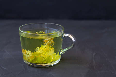 Photo pour linden flowers tea.Cup of hot herbal tea with linden fresh flowers on a black table.Healthy lifestyle.glass cup of tea with green leaves on a black background.hot drinks.copy space - image libre de droit